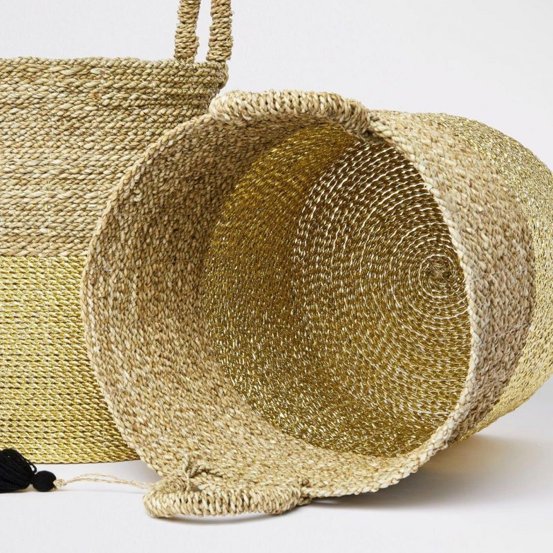 A pair of gold coloured hand-woven baskets
